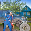 Womin working overalls tries to replace wheel at off-road car — Stock Photo #24431835