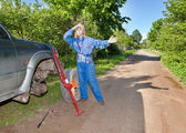 The woman in working overalls tries to replace a wheel at an off-road car — Стоковое фото