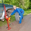 Womin working overalls tries to replace wheel at off-road car — Stock Photo #24457005
