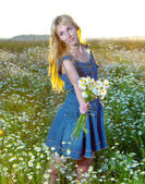 The beautiful happy young woman in the field of camomile — Stock Photo