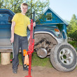 The young man, the teenager replaces a wheel at an off-road car - Stock Photo