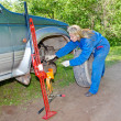 Womin working overalls tries to replace wheel at off-road car — Stock Photo #24466899