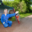 The woman in working overalls tries to replace a wheel at an off-road car — Stock Photo #24470021