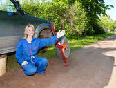 The woman in working overalls tries to replace a wheel at an off-road car — Stockfoto