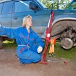 The woman in working overalls tries to replace a wheel at an off-road car — 图库照片