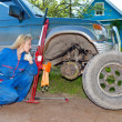 Womin working overalls tries to replace wheel at off-road car — Stock Photo #24489157