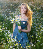 The beautiful happy young woman in the field of camomile — Foto de Stock