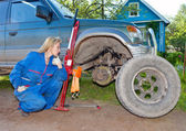 The woman in working overalls tries to replace a wheel at an off-road car — Foto Stock