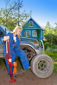 The woman in working overalls tries to replace a wheel at an off-road car, and from a rage kicks with his foot — Stock Photo