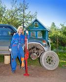La mujer en el trabajo guardapolvos intenta cambiar una rueda en un coche todoterreno — Foto de Stock