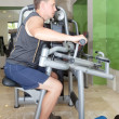 Sporting man is engaged in training in fitness center in a gym on trainers — 图库照片