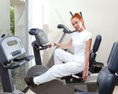 The young sporting woman in fitness center trains — Stock Photo