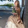 The young beautiful woman in a romantic dress in an arbor on a beach, tropics — Stock Photo