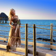 The young beautiful woman in a long dress on the wooden road over the sea — Stock Photo #27627355