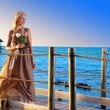 The young beautiful woman in a long dress on the wooden road over the sea — Stock Photo #27627357