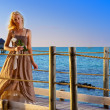 The young beautiful woman in a long dress on the wooden road over the sea — Stock Photo