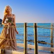 The young beautiful woman in a long dress on the wooden road over the sea — Stock Photo #27627361