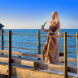 The young beautiful woman in a long dress on the wooden road over the sea — Stock Photo #27627363