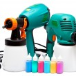 Two different construction electrical spray gun for pulverization of color and small bottles with color — Stock Photo
