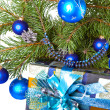 New Year's balls on branches of a Christmas tree and gifts — Stok fotoğraf