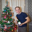 The man with a bottle of sparkling wine near a Christmas tree — Stock Photo