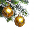 Two yellow New Year's balls and snow-covered branches of a Christmas tree — Stock Photo
