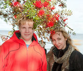 Young people at a mountain ash bush — Stock Photo