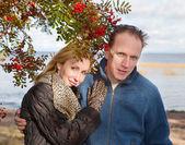 Loving couple at a mountain ash bush — Stock Photo