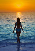 Silhouette of the woman against a sunset at ocean — Stock Photo