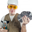 The man in working overalls in goggles and a helmet with the detachable machine and saw disk — Stock Photo