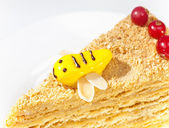 Piece of the honey cake decorated with a bee from glaze — Stock Photo