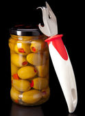 Glass jar with tinned olives and a can opener — Zdjęcie stockowe