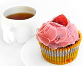 Fruitcake with a strawberry and a cup of tea — Stock Photo