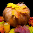 Stock Photo: Candle burns before pumpkin with maple leaf