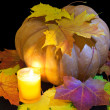 The candle burns before pumpkin with a maple leaf — Stock Photo