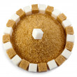 Cubes of sugar lie on circles and a heap of granulated sugar inside — Stock Photo #33713091