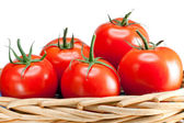 The ripened tomatoes in a wattled basket — Stock Photo