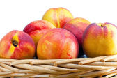 Nectarines in a wattled basket — Stock Photo