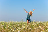 The happy young woman in the field of camomile — Stock Photo