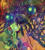 New Year's balls on branches of a Christmas tree and gifts, with a retro effect — Stock Photo