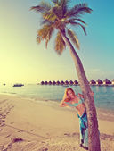 Young beautiful woman stands near palm tree, Maldives,with a retro effect — Stock Photo