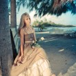 The young woman in a long sundress on a tropical beach. ,with a retro effect — Stok fotoğraf