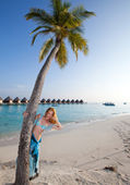 Young beautiful woman stands near palm tree, Maldives — Stock Photo