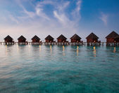 Island in ocean, overwater villas at the time sunset. — Stock Photo