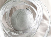 Beautiful silvery New Year's ball and decorative tape — Stock Photo