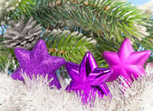 Three magenta snowflakes on al background of New Year's branches — Stock Photo
