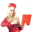 The young beautiful woman in a New Year's hat with red laptop — Stock Photo