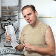 Mwith wrench looks instruction on repair gas water heater — Stock Photo #37199207