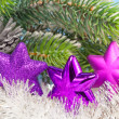 Three magenta snowflakes on al background of New Year's branches — Stockfoto