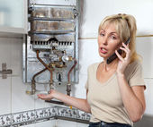 The young woman the housewife calls in a workshop on repair of gas water heater — Stock Photo